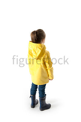 A Figurestock image of a little girl, standing in a rain coat and wellies, facing away – shot from eye level.
