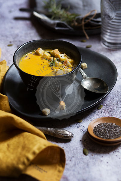 Pumpkin soup in a grey bowl front view