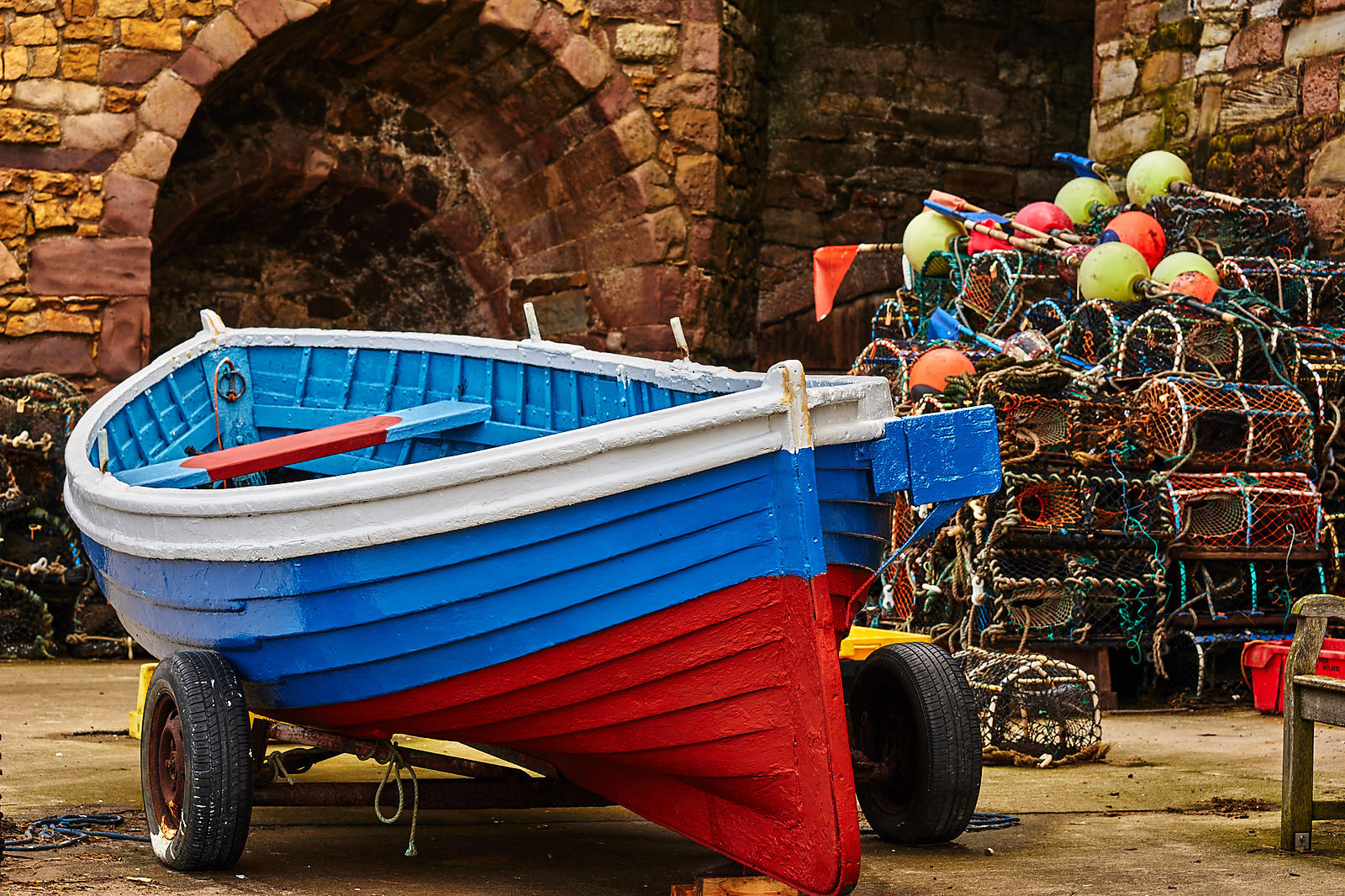 Blue and red fishing boat and lobster pots against a stone wall