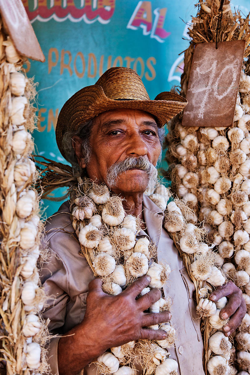 Man Holding Strings of Fresh Garlic