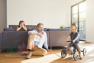 Grandfather playing with grandchildren, sitting on toy car