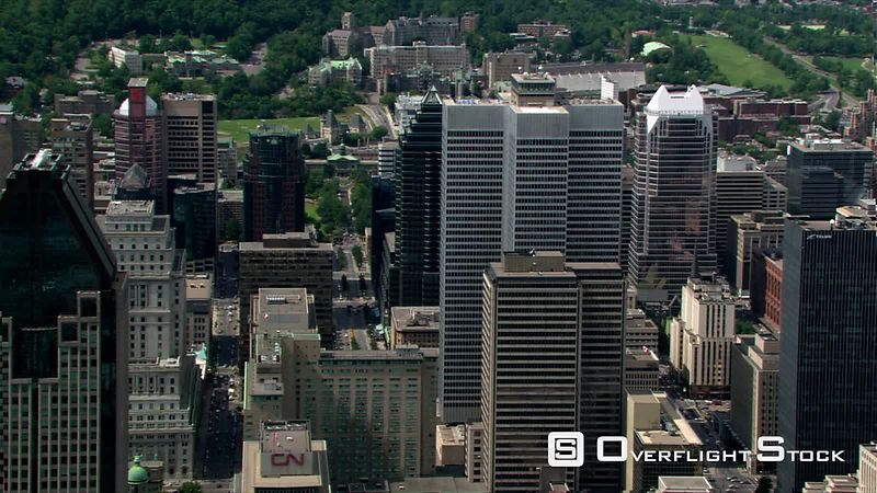Flying past skyscrapers toward green space in Montreal, Quebec.