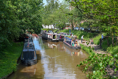 Visitors, on the warmest day of the year so far, enjoy seeing the narrowboats moored close to the Audlem Music Festival in Audlem, Cheshire, UK.