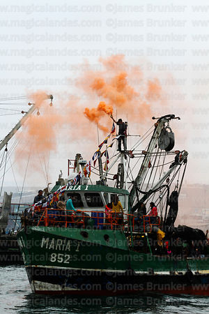 Spectators on a trawler set off smoke flares during the procession of the saints around the port, St Peter and St Paul festival, Arica, Chile