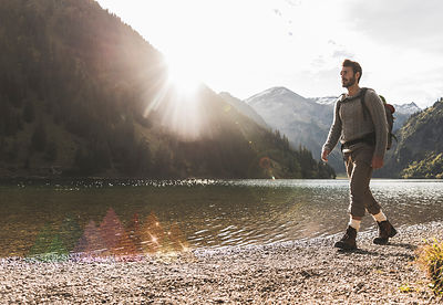 Austria, Tyrol, young man hiking at mountain lake