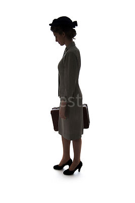 A silhouette of a 1940's woman in a suit and hat, standing with a suitcase – shot from eye-level.