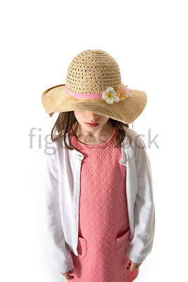 A Figurestock image of a little girl in a summer hat, looking down – shot from eye level.