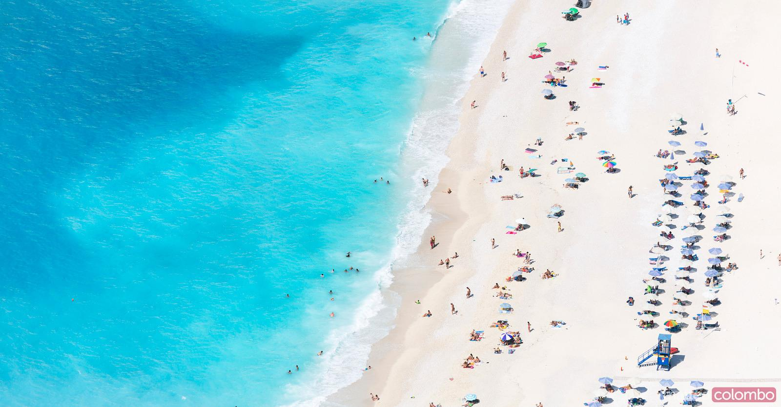 Aerial view of famous Myrtos beach crowded with tourists in summer, Greece