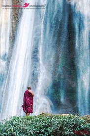 Buddhist monk praying under big waterfall, Myanmar