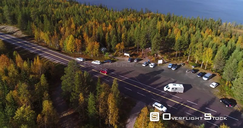 Autumn Color Road, Aerial View Following a Red Car Driving on a Fall Road, Between Colorful Autumn Forest, Sarkijarvi Lake and Fjeld Mountains, Near Pallasyllas National Park, Lapland, Finland