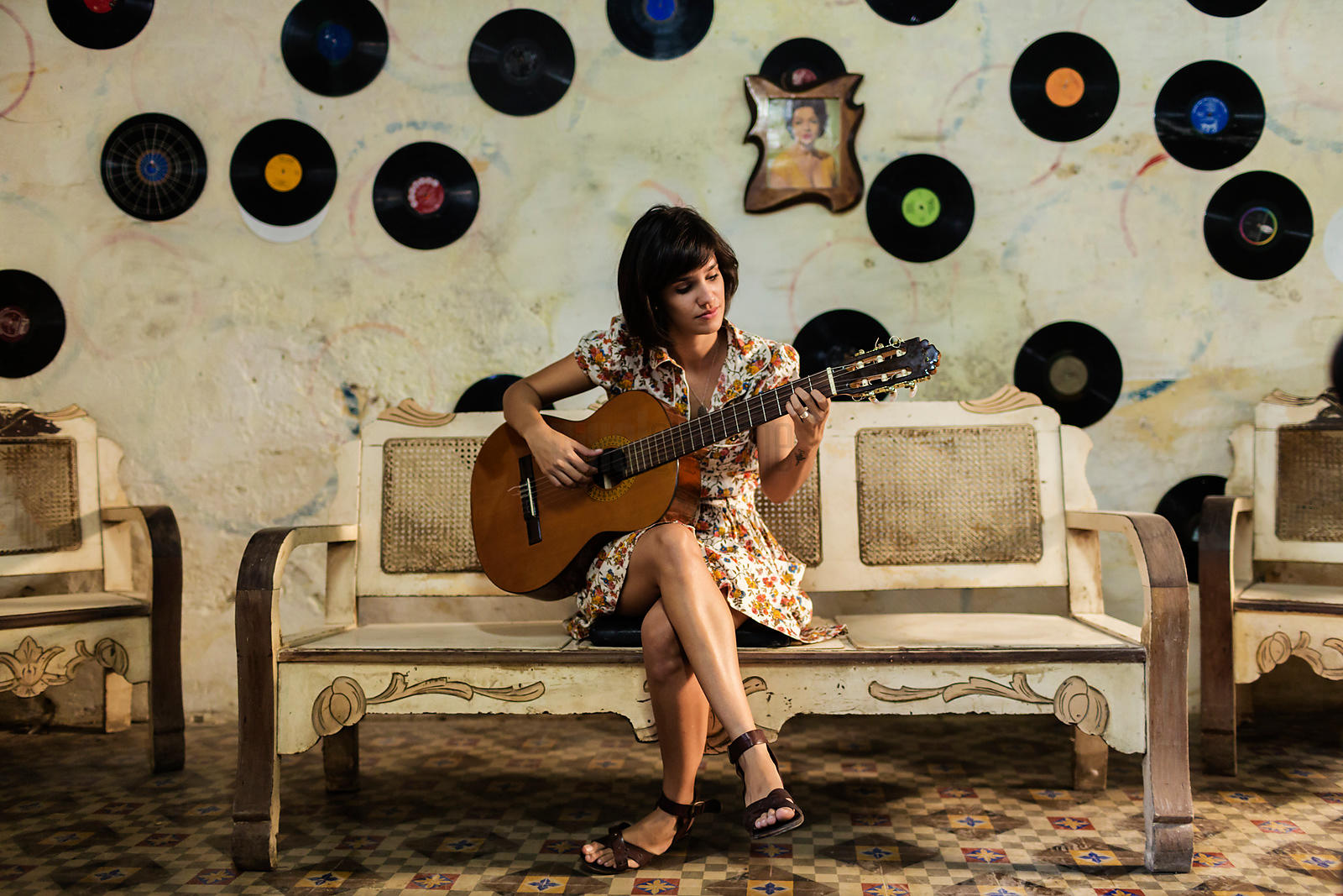 Musician Playing Guitar Sitting on Bench in Front of Wall with Hanging Records
