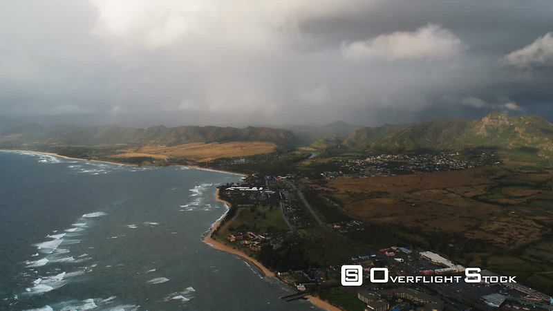 Past Kapaa under drifting clouds and pale rainbow, Hawaii.