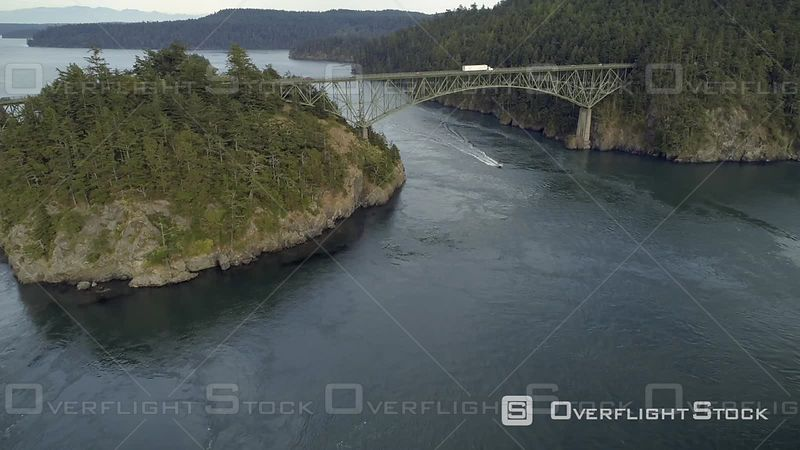 Aerial film of boat cruising under Washington State famous bridge at Deception Pass
