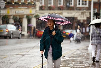 Rain Soaked Elderly Woman Under her Umbrella in  Windsor High Street