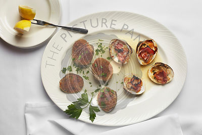 Arial photograph of stuffed clams with proscuitto and bread crumbs with a linen surface.