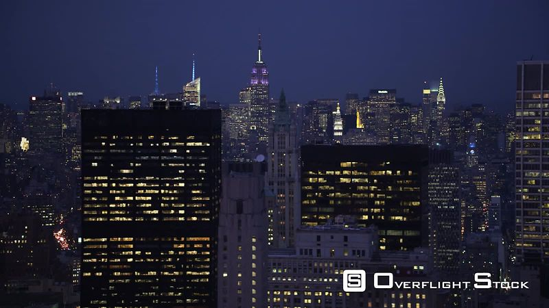 Flying past Manhattan at night, looking back at Midtown  Empire State Building in center frame.