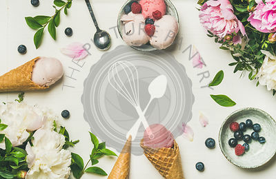 Flat-lay of pink strawberry and coconut ice cream scoops, sweet cones and peony flowers bouque
