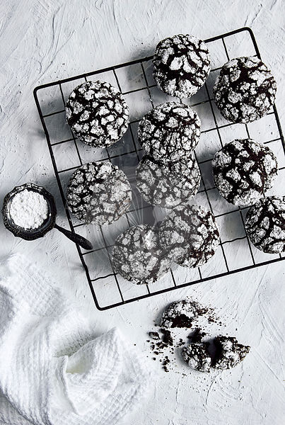 Chocolate crinkle cookies on wire cooling rack with icing sugar dusting.