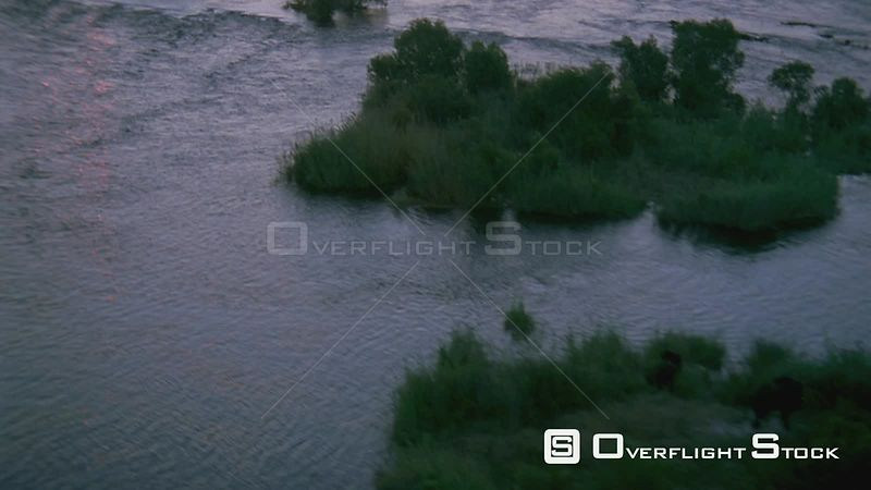 Aerial shot across flowing river to islands of vegetation with two elephants Botswana