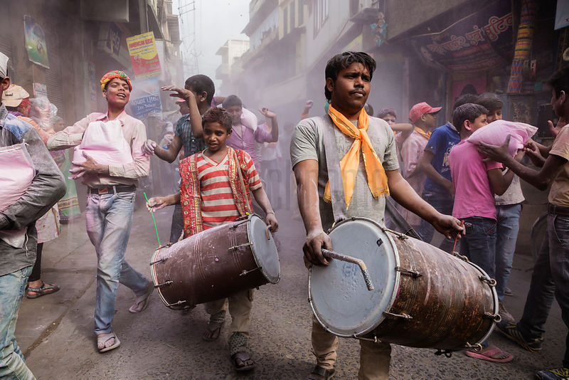 Revellers March Down a Street in Mathura During Holi Celebrations