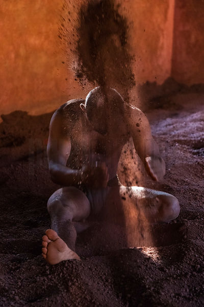 Kushti Wrestler Applying Sand to his Body During Training