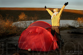 Backpacker waking up to sunny morning with arms raised by tent and lake