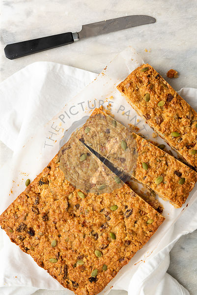 Apricot, pumpkin seed and oatmeal slice cut into strips with a knife.
