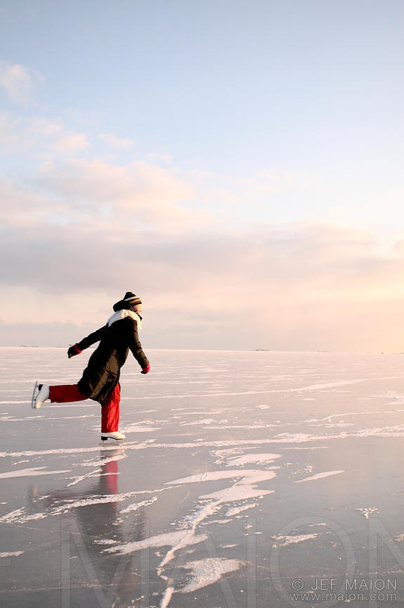 Woman ice-skating on frozen sea