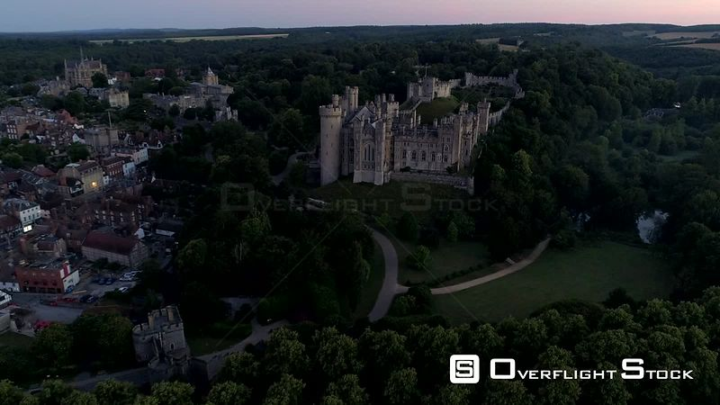 Drone moves slowly towards Arundel Castle and town in the twilight before dawn