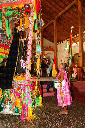 Abadesa praying to figure of San Ignacio in Jesuit Mission church after mass, San Ignacio de Moxos, Bolivia