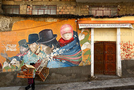 Woman carrying wooden stables for nativity scenes past indigenous mural, La Paz, Bolivia