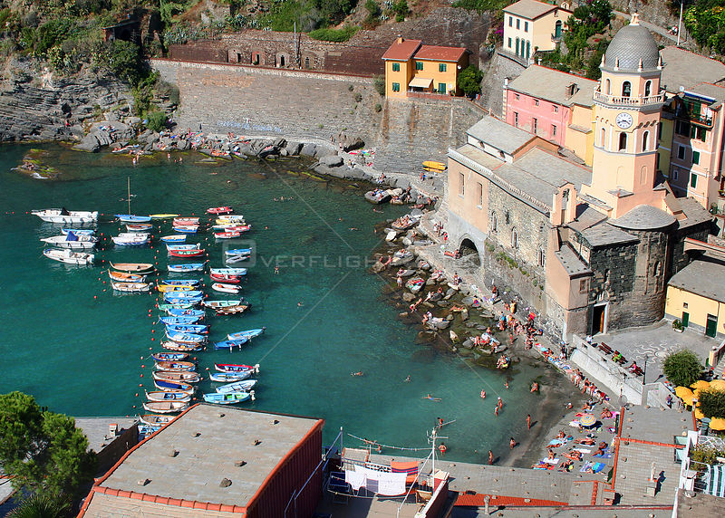 Harbour at Vernazza, with boats moored and crowds of people on the beach, Cinque Terre, Italy, 2006.