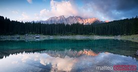 Lake Carezza at sunrise with mountain range reflected Dolomites Italy