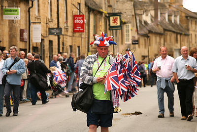 Street Vendor Carrying Flags in Chipping Campden
