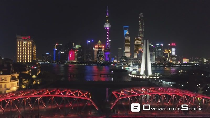 Illuminated Shanghai Downtown at Night. Lujiazui District and Huangpu River. China. Aerial View. Drone is Flying Upward. Establishing Shot.