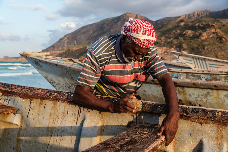 Fisherman Repairing a Boat with a Rock and Nails.