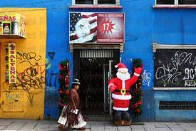 Aymara lady walking past American style thrift store and inflatable Santa Claus, La Paz, Bolivia