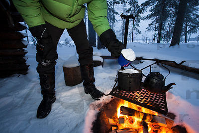 Hiker is melting water for coffee from snow