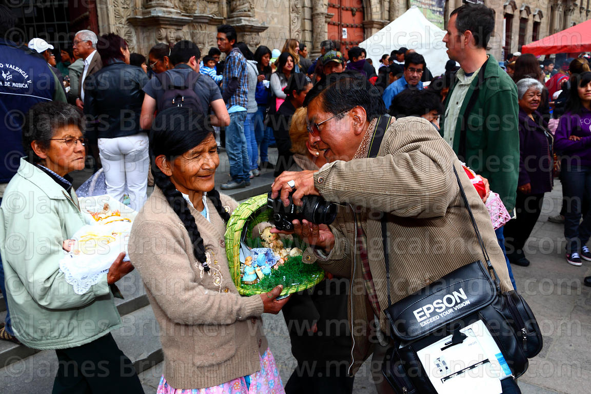 Photographer shows woman a photo of herself holding her baby Jesus figure outside church after mass for Reyes (Epiphany, January 6th), La Paz, Bolivia