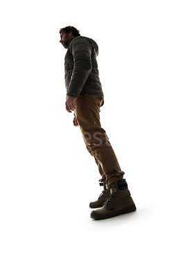 A man in outdoor clothing from the side, in semi-silhouette – shot from low level.