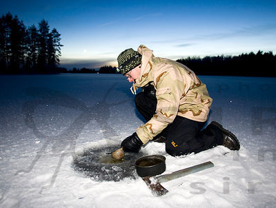 Hiker takes water for food from the ice hole