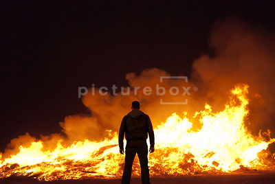 An atmospheric image of a lone man standing in front of the remains of a very large fire burning in the night.