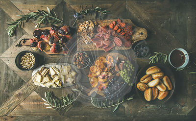 Flat-lay of holiday, friends party, gathering or family dinner table set with various wine snacks