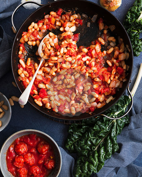 Tomatoes, cannellini beans and onions in a pan beside a bunch of silverbeet and a bowl of cherry tomatoes.