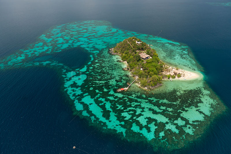 Aerial view of private tropical island surrounded by a white sandy beach and coral reefs, note helipad on end of pier, Palawan, Philippines, May 2009