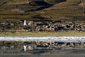 Rustic church and village of Chantani reflected in lake on edge of Salar de Uyuni, Bolivia