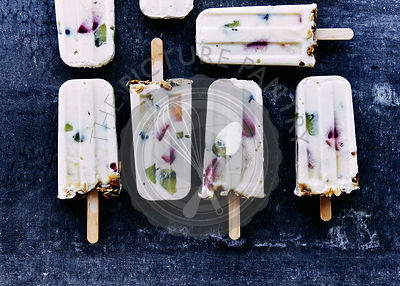 Yogurt and summer fruit popsicles topped with muesil granola. botanical ice blocks of edible flowers and herbs.