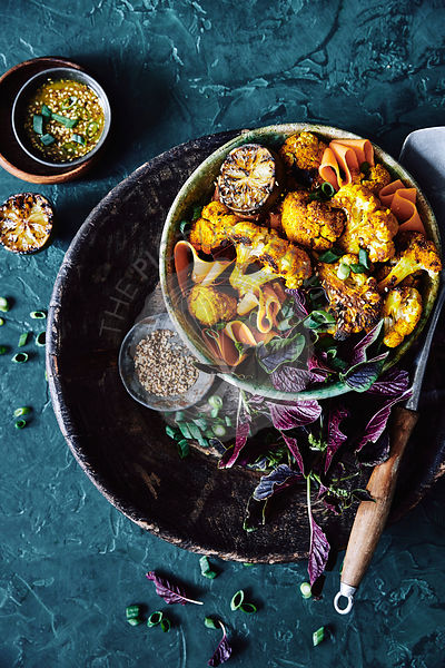 Roasted cauliflower coated in an Asian inspired turmeric, lemongrass and shallot marinade. mixed with a salad of asian greens, thin sliced cooked sweet potatoes, shallots and toast sesame seeds.