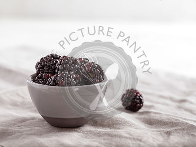 Small, gray bowl filled with fresh blackberries on a gray linen with a bright, airy background.