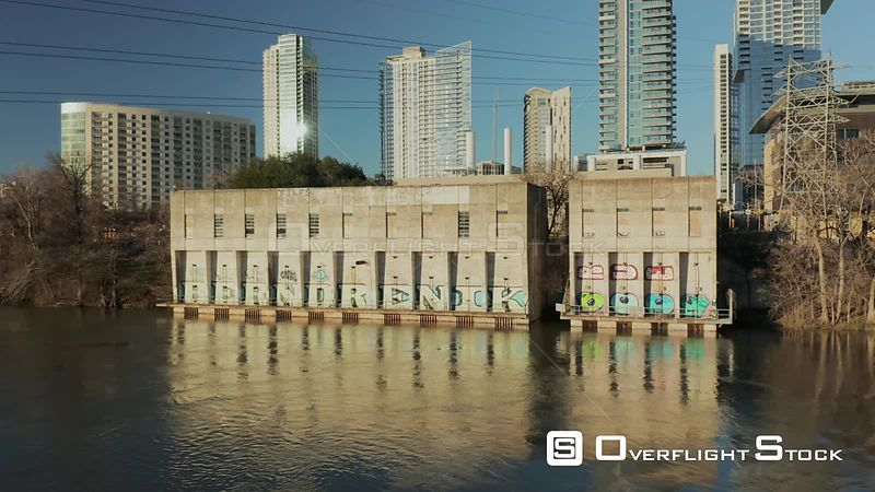 Low fly over lady bird lake with view of old power station with graffiti in downtown Austin, Texas.